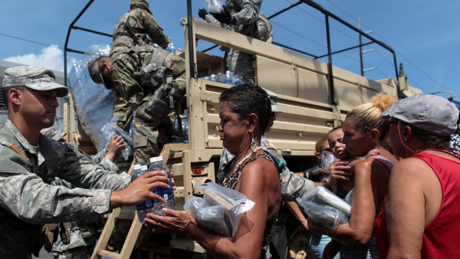 Soldiers of Puerto Rico's national guard distribute relief items to people, Sept. 24, 2017, after the area was hit by Hurricane Maria in San Juan, Puerto Rico.