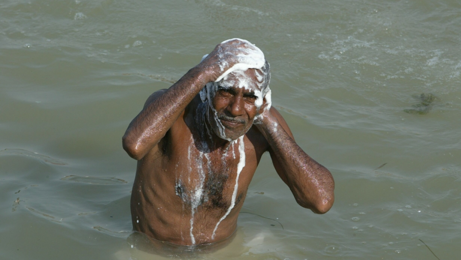 An Iraqi man bathes himself in a canal in Iraq's second largest city Basra, when electricity was cut off, August 11, 2003