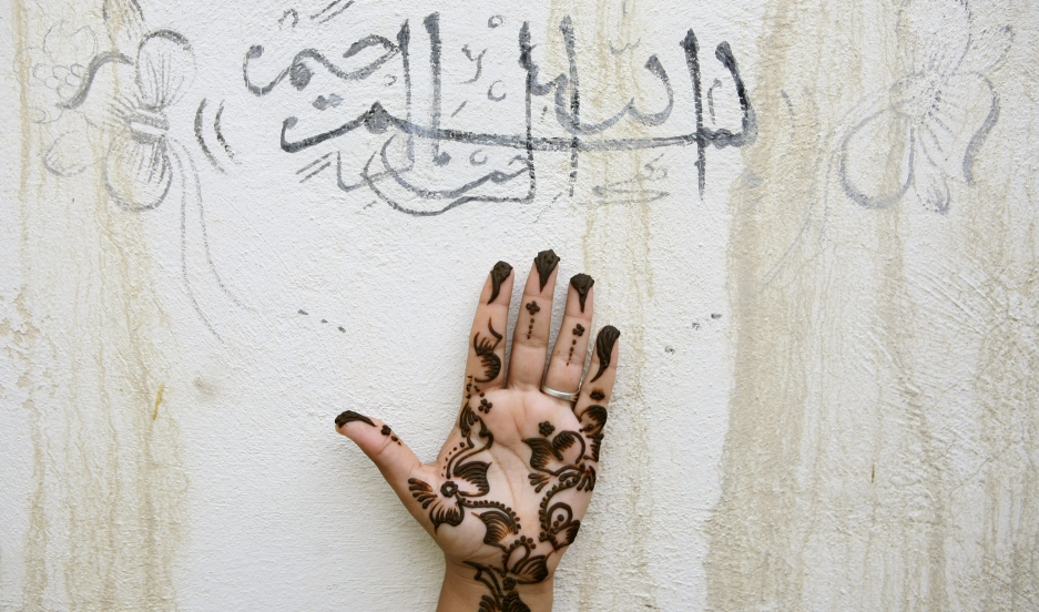 An Iranian woman holds up her hand, painted with henna, under a religious  sentence