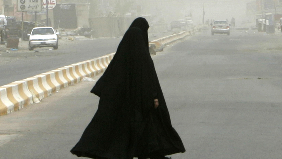 Women walk on a quiet and haze-covered street in the Amil district of Baghdad, July 8, 2007.