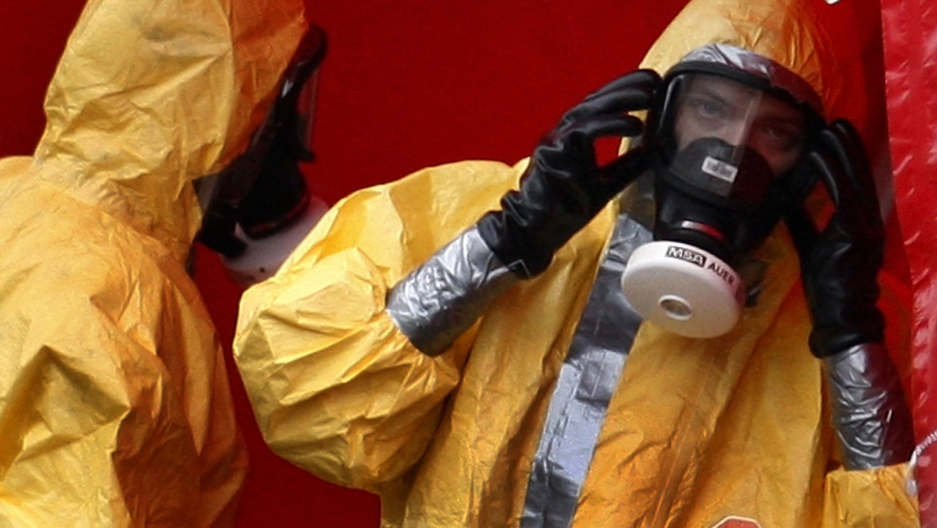 Workers in biohazard suits stand at the entry of a sealed-off poultry farm in Trumling, southern Germany, on Sep. 8, 2007. The H5N1 bird flu virus had been found in several ducks at a nearby poultry farm.