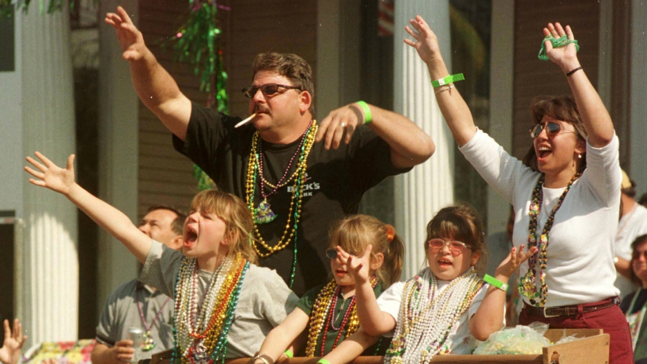 Revelers catch Mardi Gras beads during the Krewe of Thoth parade down St. Charles Avenue in New Orleans, March 5, 2000.