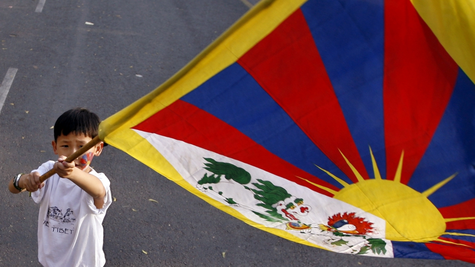 Young boy holds Tibet flag at independence protest.