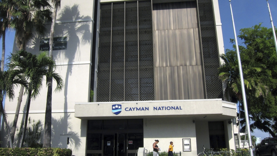 People walk out of a branch of the Cayman National Bank in George Town, Cayman Islands.