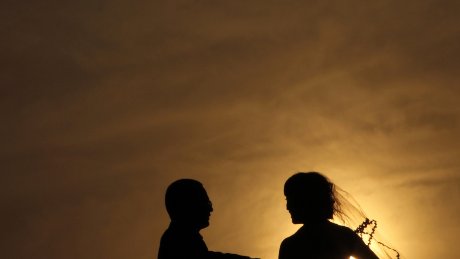 A silhouetted bride and groom