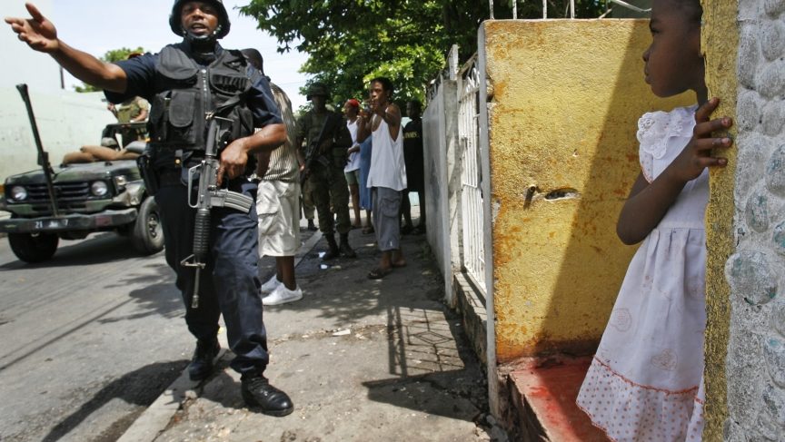 A police officer patrols the street as a little girl watches from her doorstep in the Tivoli Gardens neighborhood of Kingston, Jamaica, on May 27, 2010.