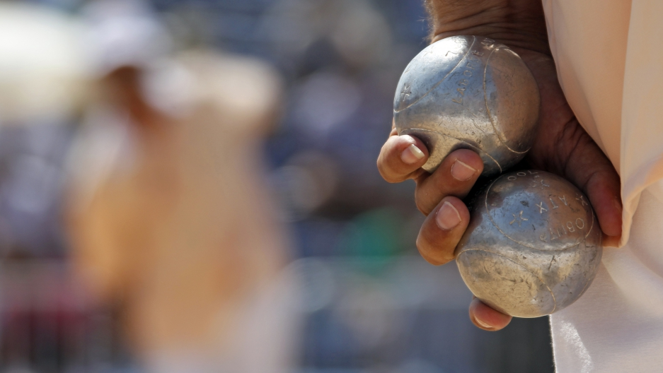 """A player holds petanque bowls during the semi-final of the """"Mondial La Marseillaise de Petanque"""" in Marseille July 8, 2010."""