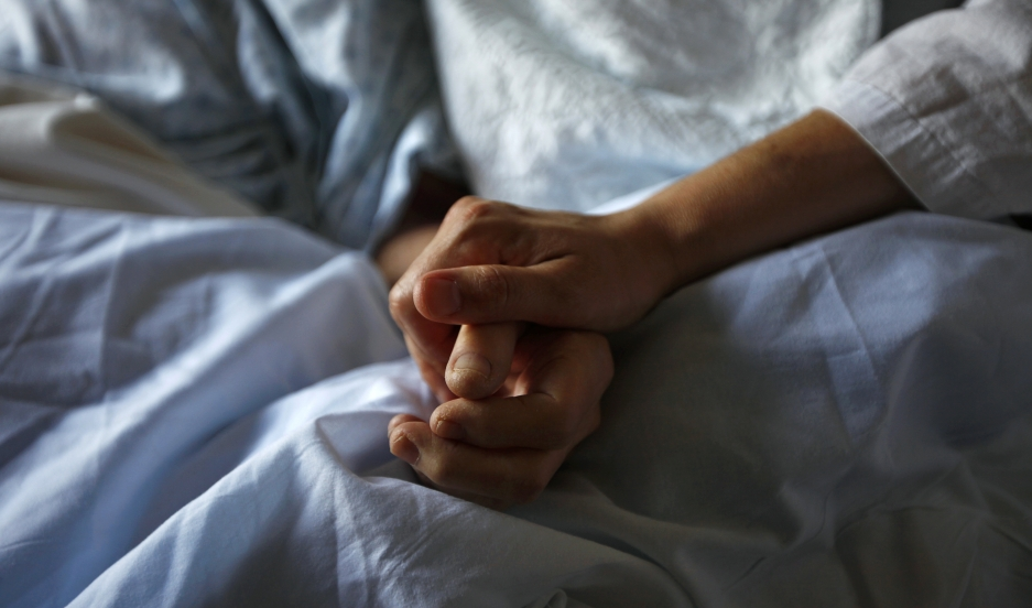 A woman holds the hand of her mother who is dying from cancer during her final hours at a palliative care hospital in Winnipeg, Canada