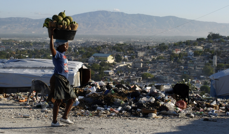 A Haitian woman carries produce to be sold in Port-au-Prince on March 15, 2011. An estimated three million people were affected by the earthquake in 2010.