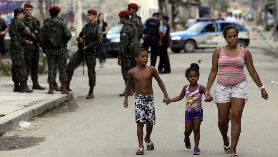 Residents walk by security forces in Cidade de Deus, Rio