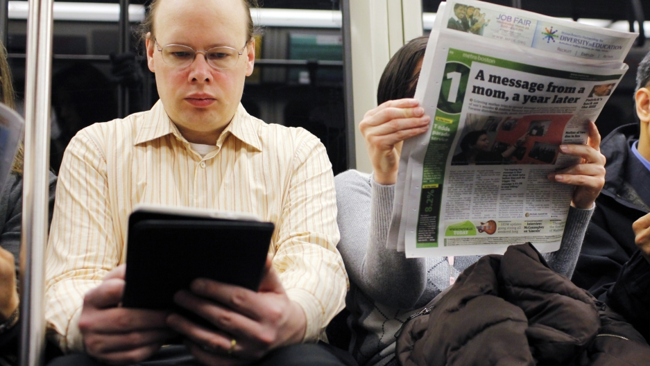 A commuter reads on a Kindle e-reader while riding the subway in Cambridge, Mass. Neuroscience says the way his brain treats reading on the Kindle is different than the way the brain processes the newspaper next to him.