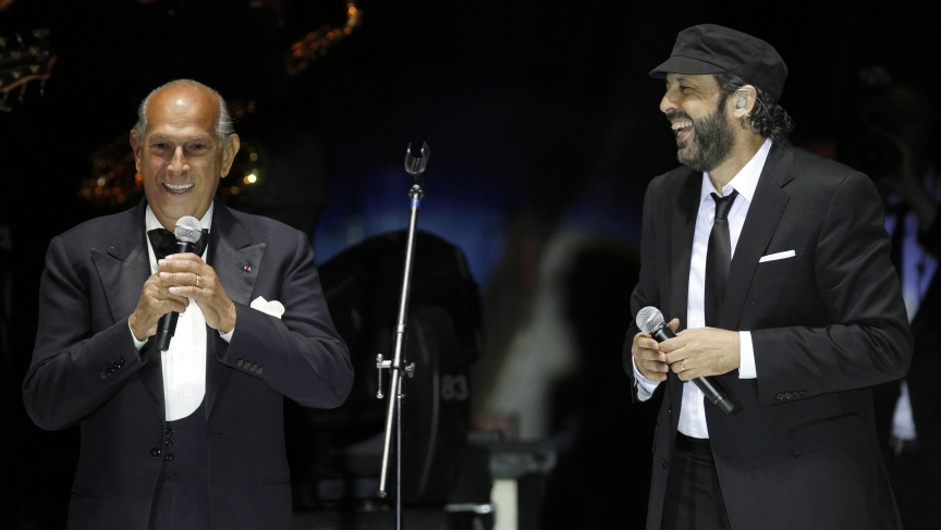 Designer Oscar de la Renta addresses the audience next to singer Juan Luis Guerra during a presentation of his collection in Mexico City in 2011.