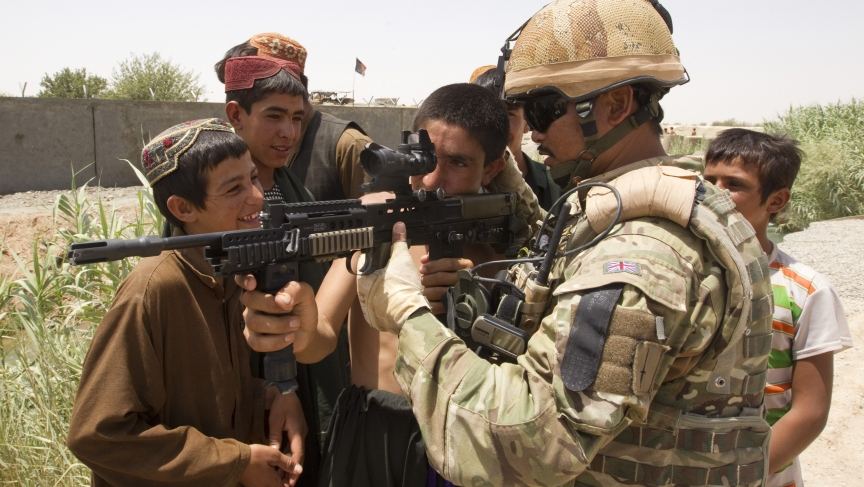 British Army Cpl. Birendra Limbu of the 2nd Battalion, The Royal Gurkha Rifles, shows his rifle to Afghan children outside the town of Lashkar Gah in Helmand province.