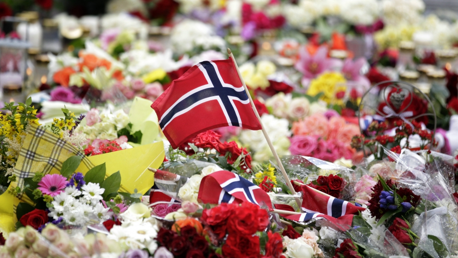 A Norwegian flag is placed amongst floral tributes outside the Oslo cathedral July 24, 2011. A right-wing zealot who admitted to bomb and gun attacks in Norway that killed 92 people on Friday claims he acted alone, Norway's police said on Sunday.