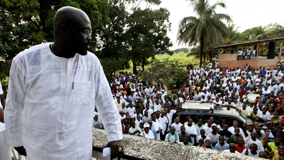 George Weah, a former soccer star, warlord and model looks on as he stands at the balcony after a news conference at his headquarters in Monrovia November 5, 2011.
