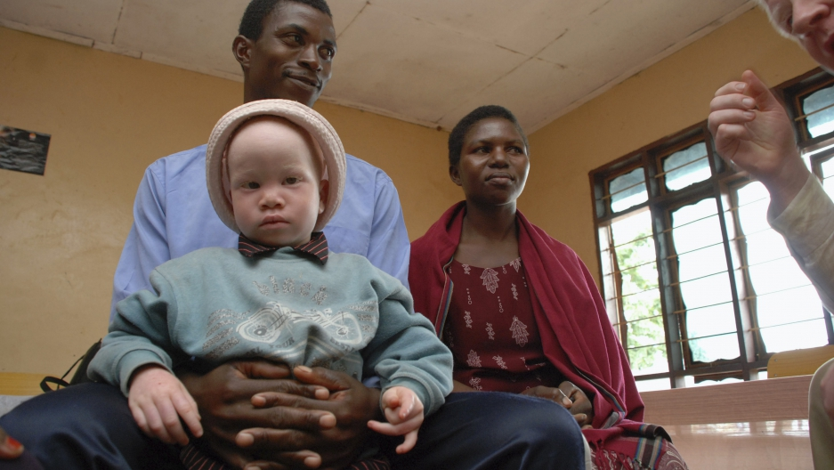 Elias Stariko (L) sits next to wife Farida Bwire, as he holds their son at the Golden Valley English Medium School, a school sponsored by Under the Same Sun (UTSS), in Geita November 24, 2011.