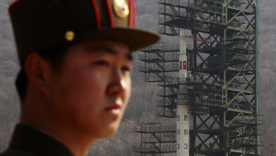 A soldier stands guard in front of the Unha-3 rocket sitting on a launch pad at the West Sea Satellite Launch Site in Pyongyang.