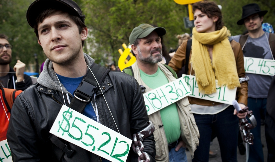 Occupy Wall Street demonstrators wear signs around their neck representing their student debt during a protest against the rising national student debt in New York on April 25, 2012.