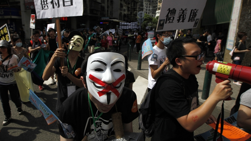 "Pro-democracy demonstrators wearing Anonymous masks hold placards during a protest march demanding universal suffrage for Macau on May 1, 2012. The placard reads ""Vote for Chief Executive."""