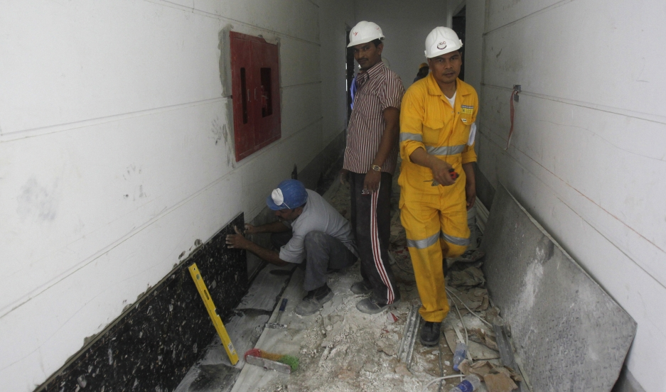 Laborers work at a construction site in Doha on June 18, 2012.