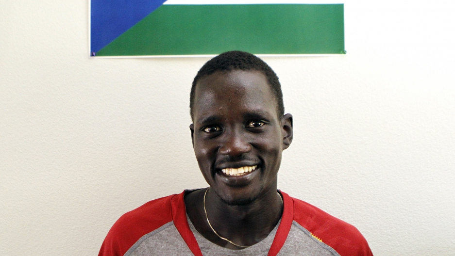 Guor Marial, 28, smiles in his apartment under a South Sudan flag in Flagstaff, Arizona July 21, 2012. The marathon runner born in what is now South Sudan ran under the Olympic flag in London.