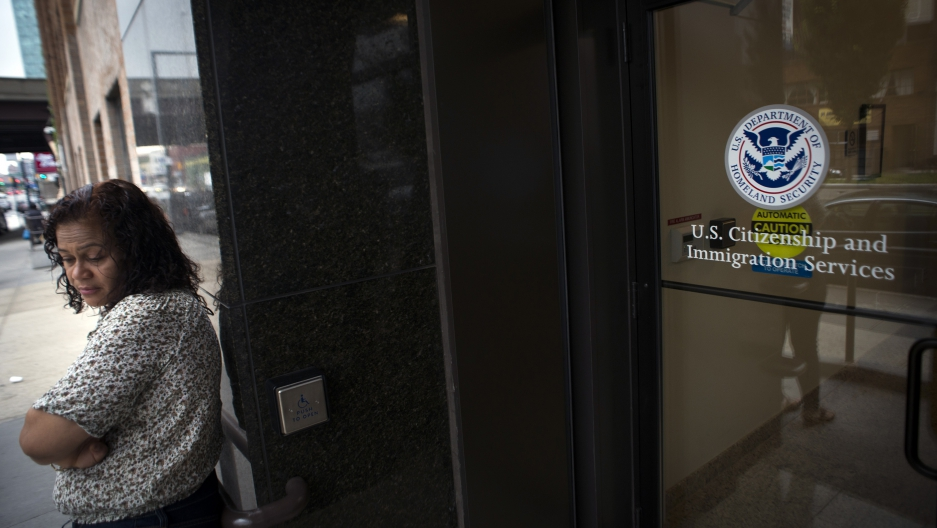 A woman stands in front of the doors of the US Citizenship and Immigration Services offices in New York.