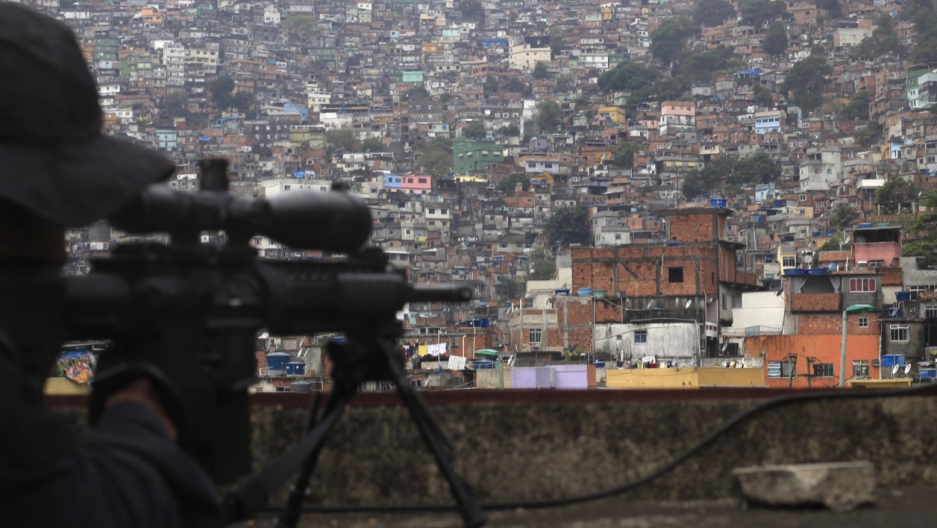 A sniper aims his gun at Rio de Janeiro's Rocinha slum during the inauguration of its so-called peacekeeping unit program in September 2012.