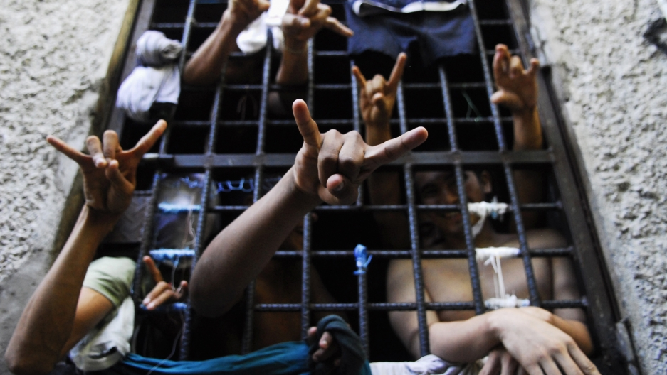 Prisoners flash the MS-13 Mara Salvatrucha street gang hand sign from inside a jail cell at a police station in San Salvador.
