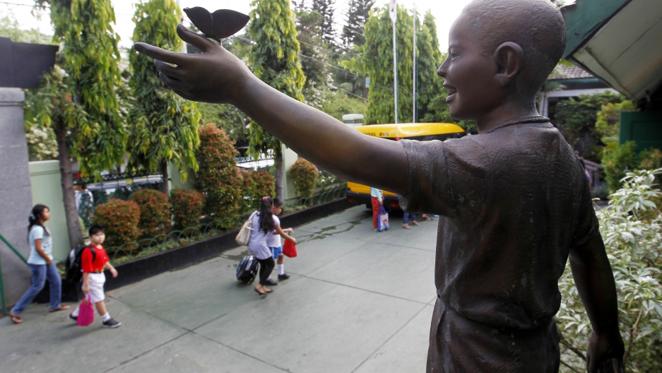 Statue of a young boy looking out over school yard