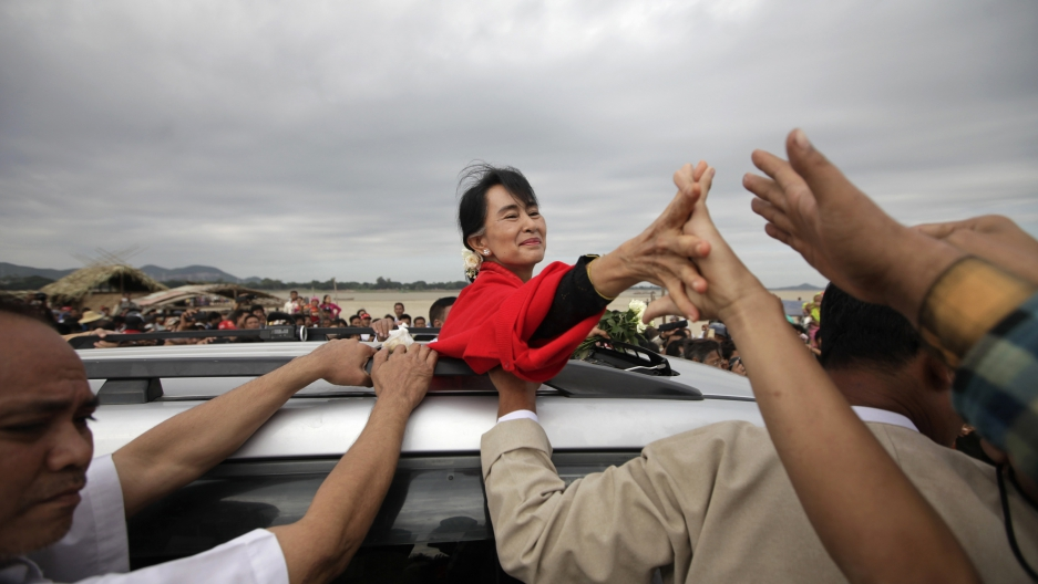 Myanmar pro-democracy leader Aung San Suu Kyi shakes hands with supporters after giving a speech in Monywa November 30, 2012.
