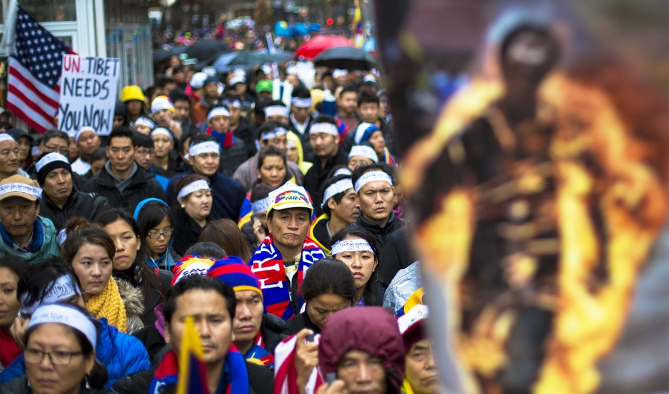 Protesters stand behind a photo of a victim of self-immolation during a 2012 march in New York City in support of Tibet.