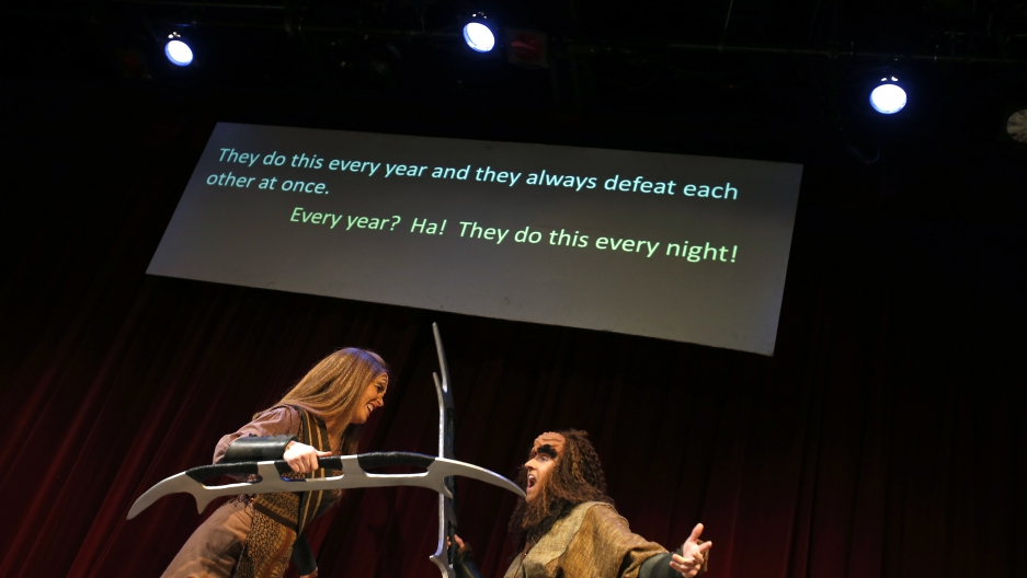 "Performers Ali Kidder-Mostrom (L) and David Coupe perform a fight scene as a translation of their dialogue is projected on a screen during a performance of ""A Klingon Christmas Carol"" in Chicago, December 20, 2012"