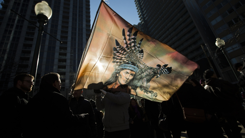 "First Nations protesters are silhouetted behind a flag in a ""Idle No More"" demonstration in Toronto."