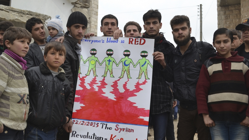 Syrian demonstrators pose with a sign in Kafr Nabl, near Idlib.