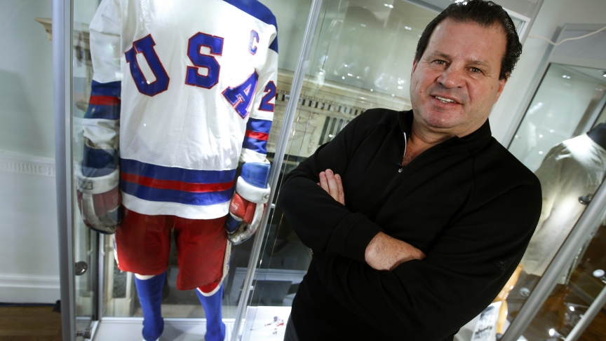 """Mike Eruzione, captain of the 1980 gold medal winning U.S. Olympic ice hockey team poses next to the jersey and uniform he wore when the U.S. defeated the Soviet Union in what is known as the """"Miracle on Ice"""" at Heritage Auctions in New York City"""