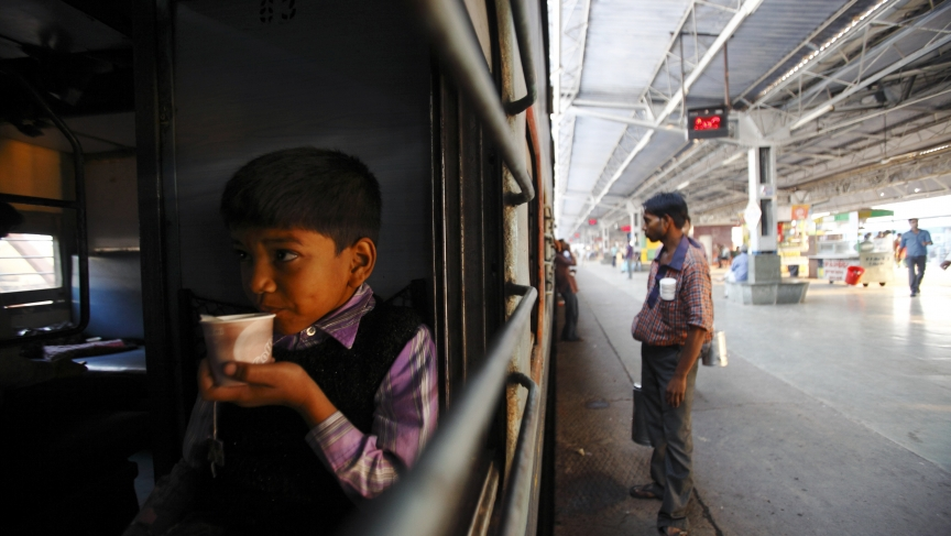 A young boy drinks tea in the early morning inside a train at Agra Cantt Railway Station in Agra, India.