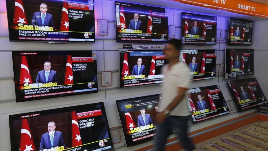 "A news conference of Turkish Prime Minister Tayyip Erdogan is screened on televisions at an electronics shop in Istanbul September 30, 2013. Erdogan announced a so-called ""democratization package"" that would allow for education in languages other than Tur"