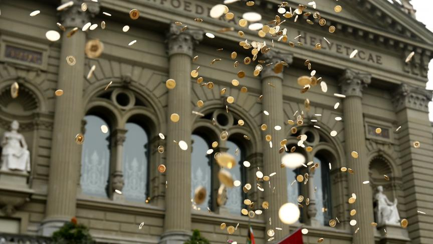 Five cent coins are pictured in the air in front of the Federal Palace in Bern, Switzerland, during an event organised by the committee that delivered 126,000 signatures to the parliament to propose a minimum monthly disposal household income of CHF 2,500