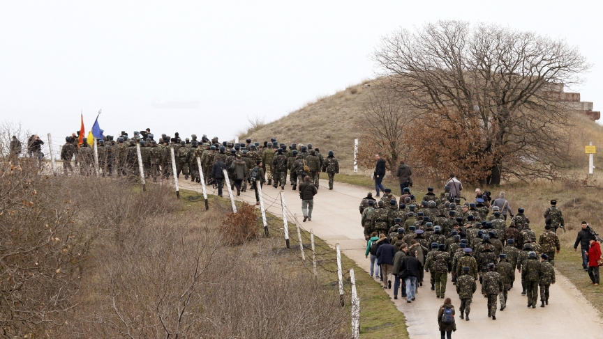 Ukrainian servicemen march away from the Belbek Sevastopol International Airport in the Crimea region on March 4, 2014. A column of unarmed Ukrainian servicemen arrived at the base for negotiations with Russian troops on Tuesday, local media reported. The