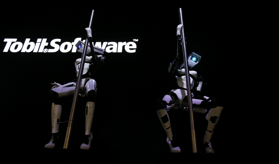 """Female"" robots Tessy and Tess wear white stiletto heels and pole dance during a demonstration at the Tobit Software stand at the 2014 CeBIT trade fair in Hanover, Germany."