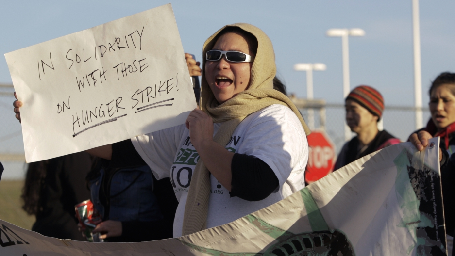 "Woman holds up sign that readers ""In solidarity with those on hunger strike"""