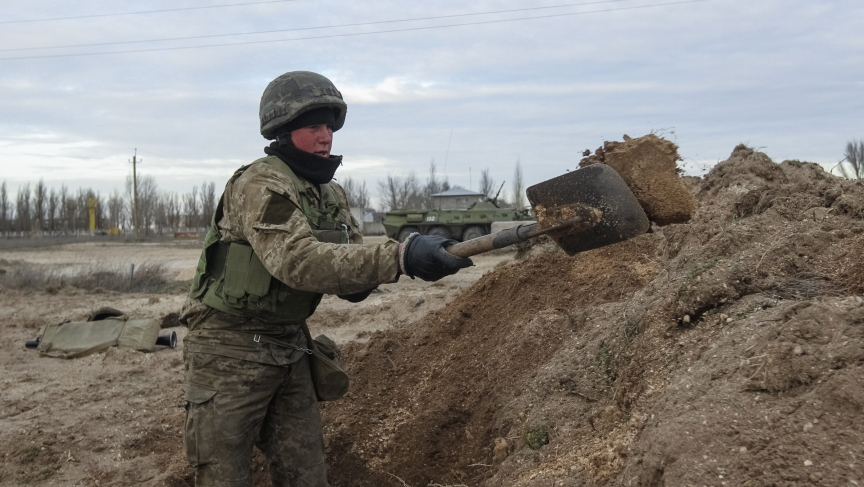 """A Ukrainian serviceman digs a trench at a checkpoint facing Russian-occupied Crimea. Ukraine's small frontier detachments would have difficulty stopping an all-out Russian attack, but would more likely be by-passed and isolated, on the """"Crimean model"""" of"""