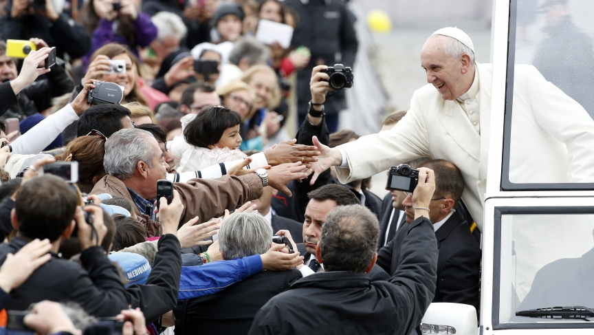 Pope Francis reaches out to greet the faithful in Saint Peter's Square at the Vatican on March 26, 2014.