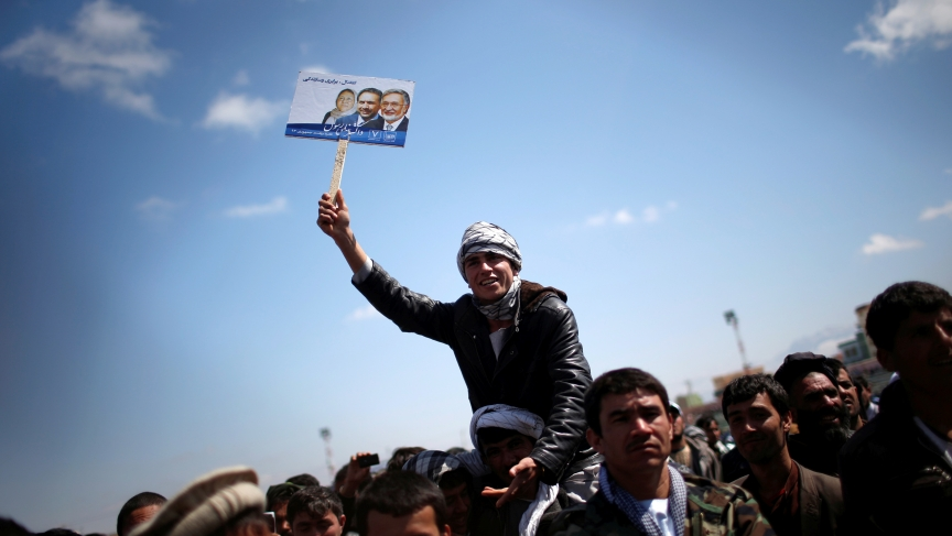 A supporter of Afghan presidential candidate Zalmai Rassoul holds his picture during an election rally in the city of Mazar-i-Shariff, in northern Afghanistan on March 27, 2014. The Afghan presidential election will be held on April 5.