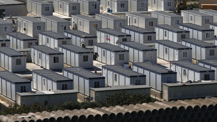 """African immigrants walk among rows of prefabricated container houses, which have replaced scores of tents, at the open centre for immigrants formerly known as """"Tent City"""" in Hal Far, outside Valletta March 27, 2014. In 2013"""