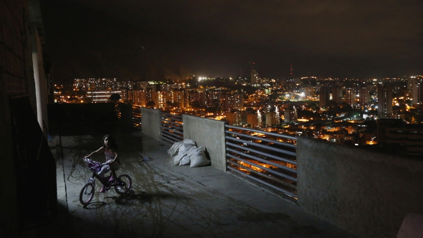 "A girl rides a bicycle on a balcony in the ""Tower of David"" skyscraper."