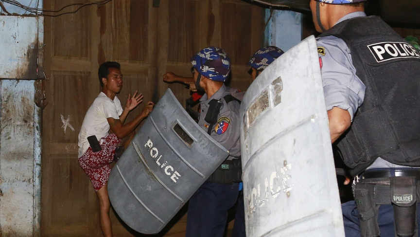 Riot police attack a man during an anti-Muslim riot in Hlegu, outside Yangon, in April. More sectarian riots flared up in Myanmar in July.
