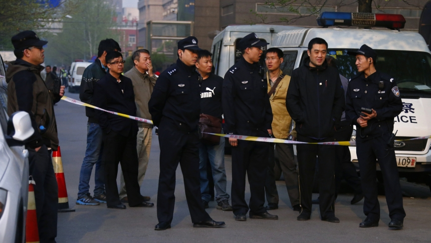 Police officers stand outside as Chinese human rights lawyer Ding Jiaxi stands trial at a court in Haidian District, Beijing, April 8, 2014.
