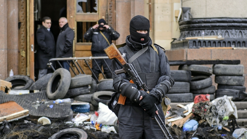 A masked armed man, representing Ukrainian special forces, stands guard outside the regional administration building in Kharkiv, April 8, 2014.
