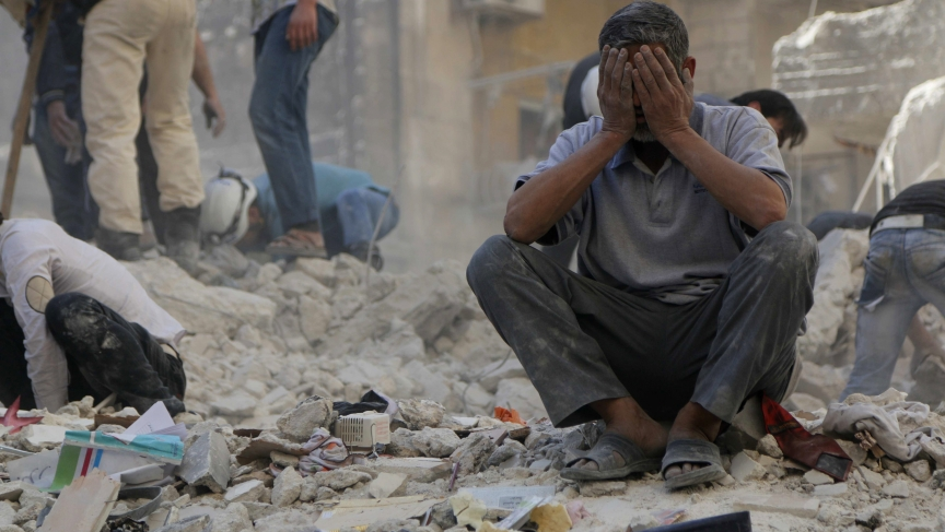 A man sits amid debris after an apparently random air attack by forces loyal to Syria's President Assad in Aleppo earlier this week. The civil war has no end in sight.